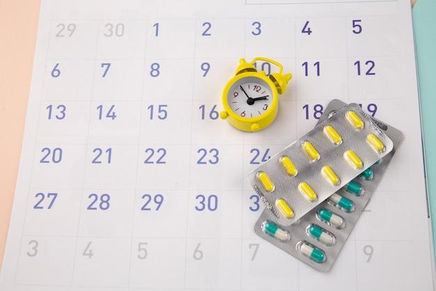Tempo di controllo per prendere le pillole. orologio con pillole su un calendario mensile.
