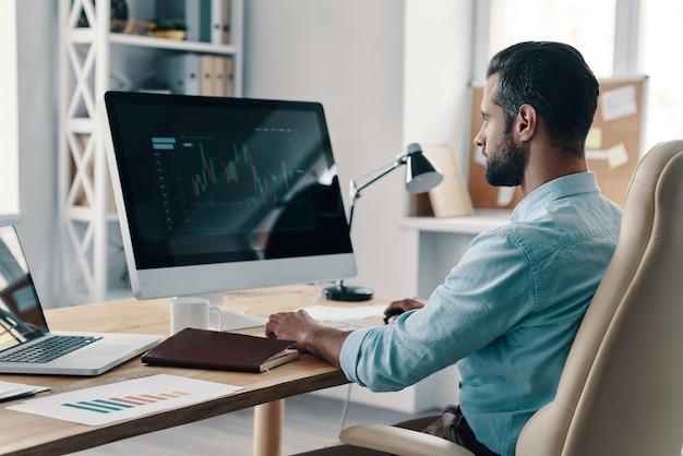 Capitale di controllo. giovane uomo d'affari moderno che analizza i dati utilizzando il computer mentre è seduto in ufficio