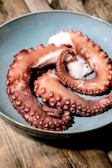 Tentacoli cotti di polpo su piatto di ceramica blu su superficie di legno marrone. avvicinamento