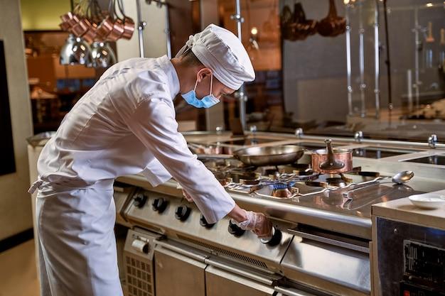 Cuocere chinandosi sul fornello girando una manopola