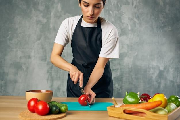 Cuocere in grembiule nero cucinare una dieta sana per l'insalata