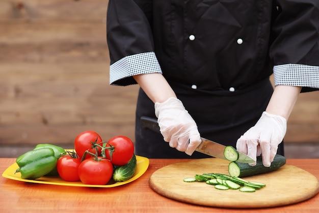 Il cuoco taglia le verdure fresche dell'azienda agricola per la cena sul tavolo