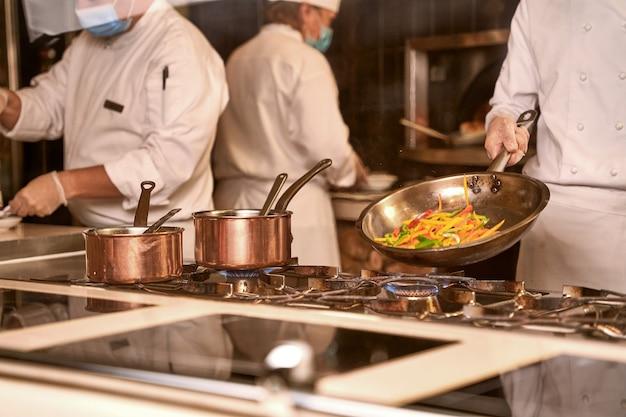 Cuocere le verdure saltando in padella in cucina