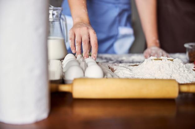 Mano del cuoco che prende un uovo da una scatola