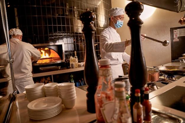 Cuocere tenendo il mestolo sopra una padella in cucina