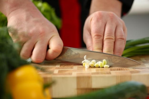 Cook tiene in mano un coltello e taglia sul tagliere cipolle verdi per insalata o zuppa di verdure fresche con vitamine. ricettario vegetariano e dell'alimento crudo nel concetto popolare della società moderna.