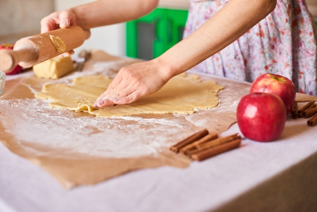 Cucina a casa. pasta d'impastamento della donna per la torta di mele sul tavolo da cucina. stile rustico