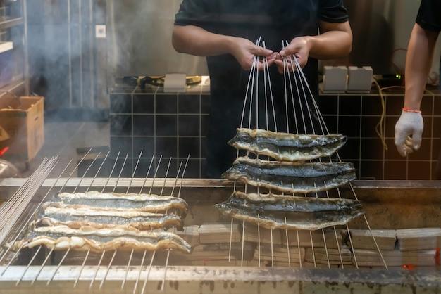 Il cuoco sta arrostendo le anguille
