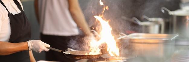 Il cuoco in cucina tiene la padella in cui brucia il fuoco.