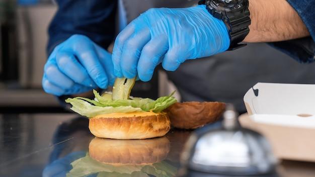 Cuocere preparando hamburger, aggiungendo sottaceti, food truck