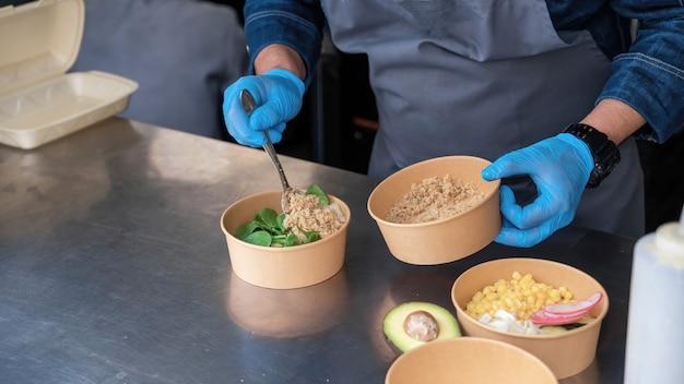 Cuocere preparando l'insalata, aggiungendo ingredienti, food truck
