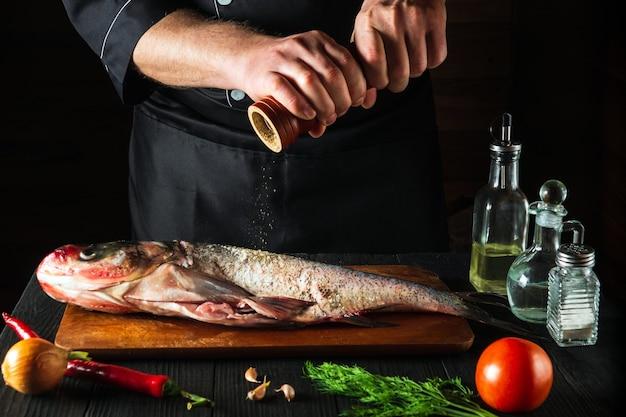 Il cuoco prepara pesce fresco carpa bighead spolverando pepe. preparazione per cucinare cibo per pesci. ambiente di lavoro nella cucina del ristorante o del bar