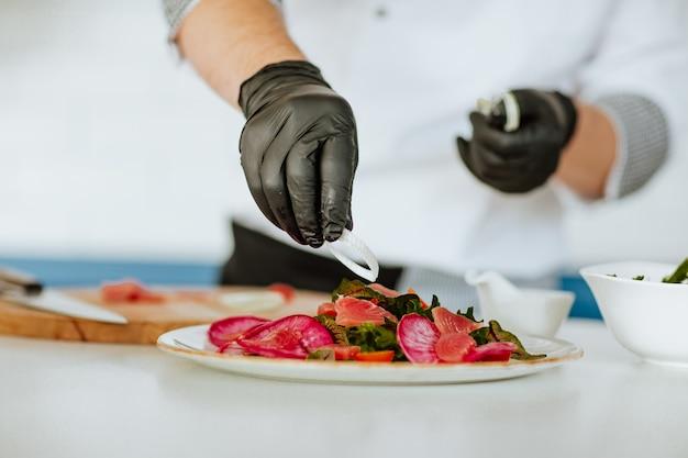 Mani del cuoco in uniforme bianca con guanti medici neri che fanno insalata sulla cucina.