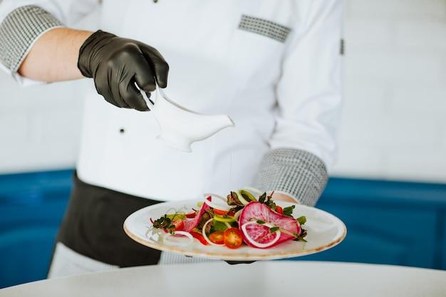 Le mani del cuoco in uniforme bianca con guanti medici neri versano il condimento per l'insalata.