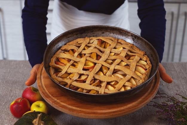 Cook mostra una torta al forno su una tavola di legno