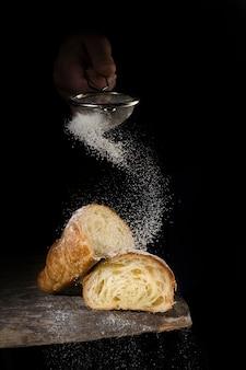 Cook spruzza con croissant in polvere, croissant su fondo di legno scuro.