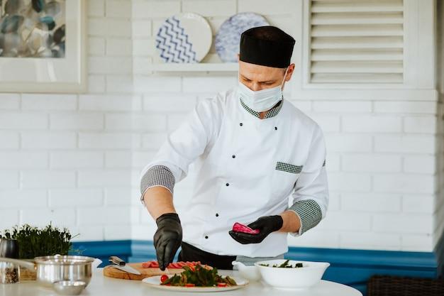 Cucina in uniforme bianca con guanti medicali neri e maschera che fa insalata in cucina.
