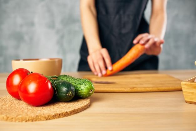 Cuoca la donna che cucina il tagliere di un'alimentazione sana