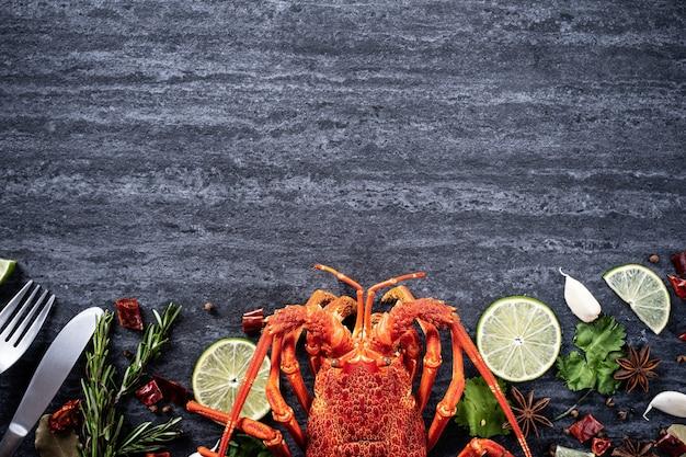 Aragosta bollita cotta, cena deliziosa con pasto a base di pesce con coltello e forchetta su sfondo di ardesia in pietra nera, design del menu del ristorante, vista dall'alto, dall'alto
