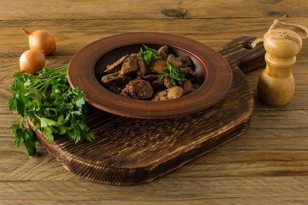 Fegato di pollo cotto con cipolla su un piatto servito su scrivania in legno. stile rustico.