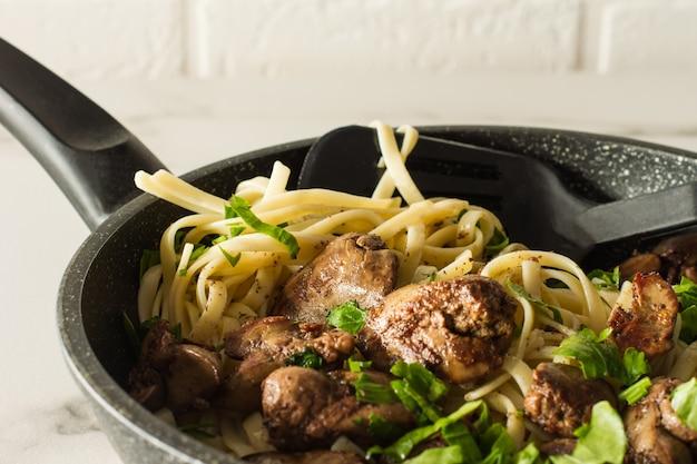 Fegato di pollo cotto con cipolla e spaghetti su una penna di cottura con prezzemolo. cena gustosa in famiglia.