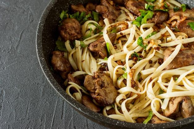 Fegato di pollo cotto con cipolla e spaghetti su una penna di cottura con prezzemolo.