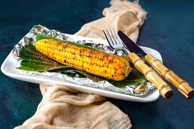Pannocchie di mais cotte su un fuoco aperto mais dolce arrostito con spezie vista dall'alto piatta verdure grigliate...