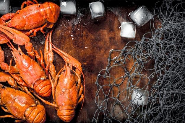 Aragosta cotta con ghiaccio e rete da pesca su un vassoio di legno su un tavolo rustico.