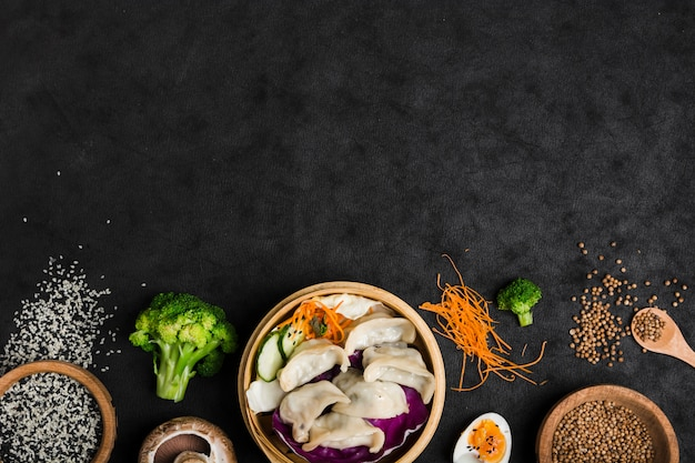 Gnocchi cotti all'interno del piroscafo di bambù con uova; broccoli; semi di sesamo e coriandolo su sfondo nero trama