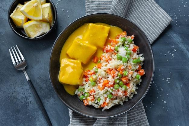 Bocconcini di pesce cotto con verdure crude e salsa al curry serviti in una ciotola. avvicinamento.