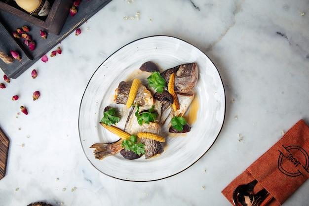 Pesce di mare gourmet cotto su un piatto sul tavolo