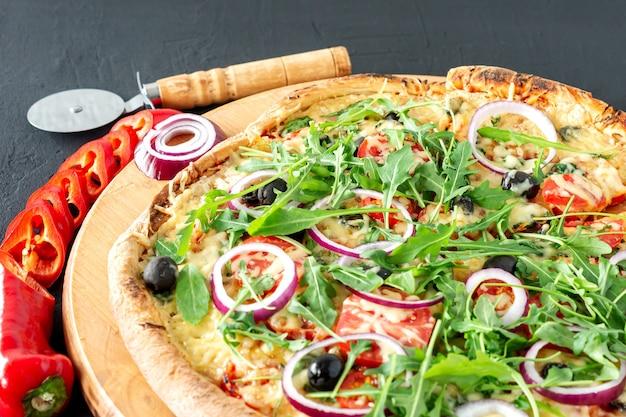 Pizza calda cotta con peperoni, pomodori, olive nere, rucola e mozzarella su tavola di legno.