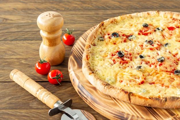 Pizza calda cotta con peperoni, pomodori, olive nere e mozzarella su tavola di legno.