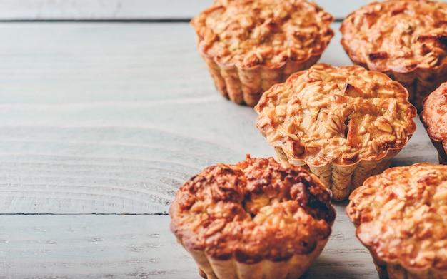 Muffin di farina d'avena cotta su fondo di legno chiaro.