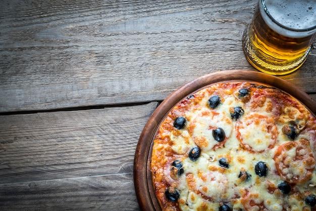 Pizza cotta con un bicchiere di birra