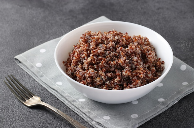 Quinoa rossa cotta in un piatto bianco su sfondo grigio scuro. avvicinamento