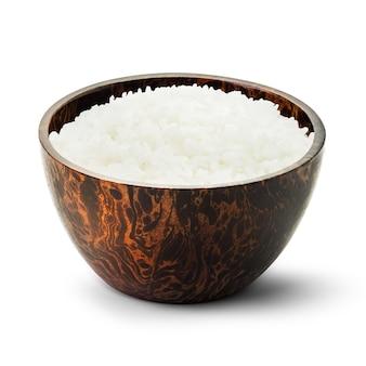 Riso cotto in una ciotola di legno isolato su bianco