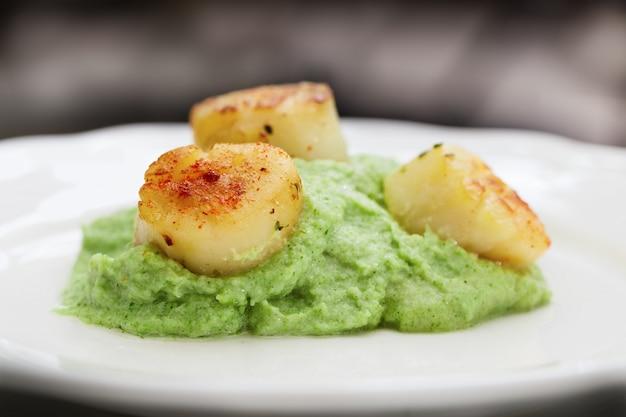 Capesante cotte con purè di patate di verdure sul piatto bianco