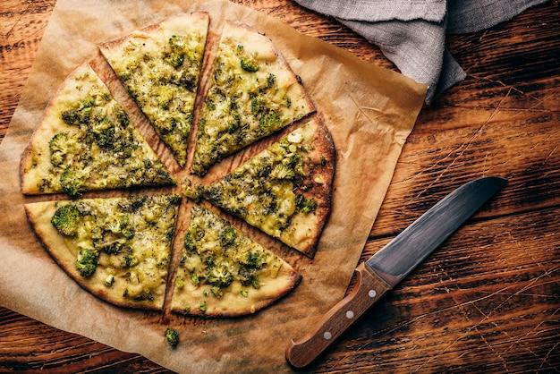Pizza broccoli e formaggio cotta e affettata su carta da forno. vista dall'alto