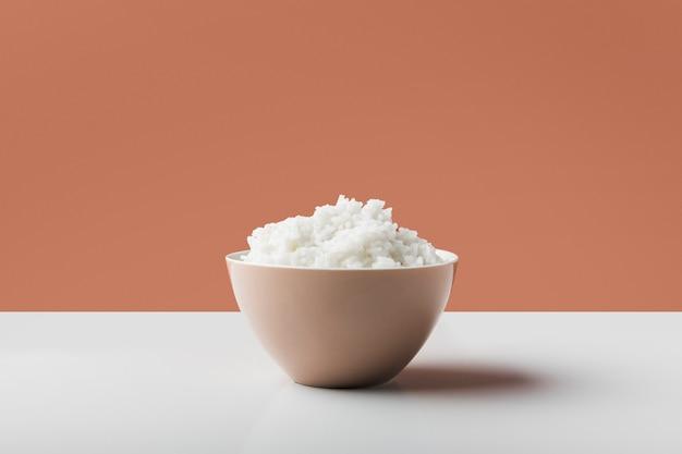 Riso bollito bianco cucinato nella ciotola sulla tavola bianca contro fondo marrone