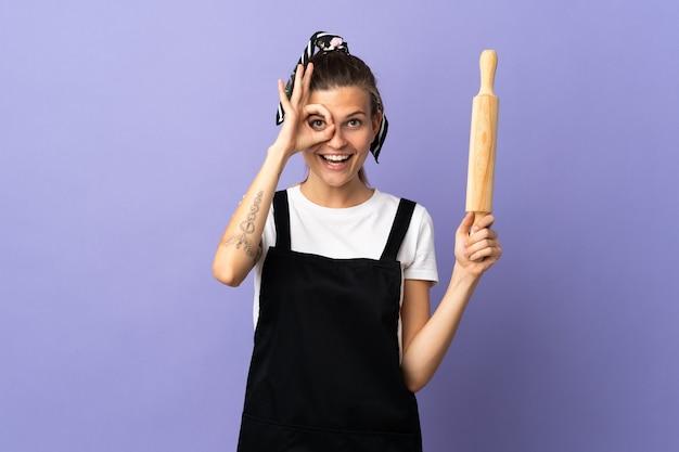Donna slovacca del fornello isolata sulla parete viola che mostra segno giusto con le dita