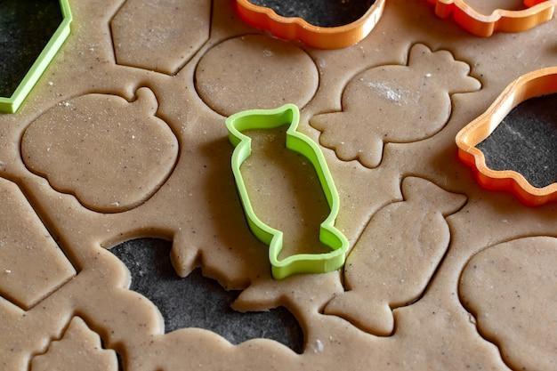 Il tagliabiscotti taglia i biscotti di pan di zenzero dall'impasto per halloween