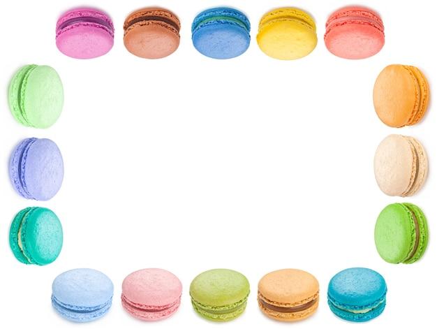 Macarons colorati con cornice di biscotti su sfondo bianco