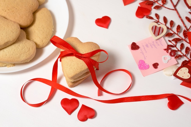 Cuore di biscotto legato con nastro rosso per il giorno di san valentino, cottura per le vacanze. vista dall'alto di cuori decorativi.