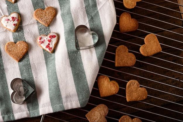 Cuori di biscotti sul tovagliolo di stoffa bianco e verde con cuori di forme metalliche su griglia metallica per san valentino