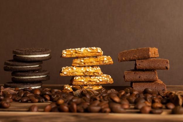 Biscotti su un tavolo marrone di un albero bruciato con chicchi di caffè sparsi sul tavolo.