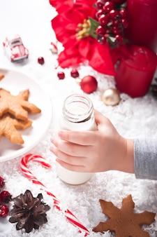 Biscotti, bastoncino di zucchero e latte per babbo natale sul tavolo sullo sfondo della decorazione di natale