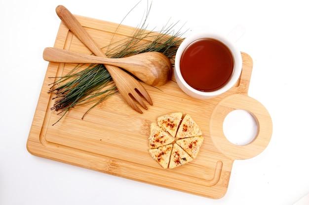 Biscotti e tazza di te sul vassoio in legno