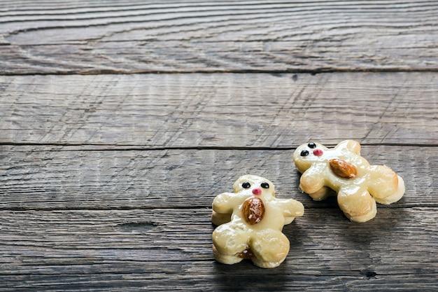 Biscotti sotto forma di personaggi divertenti su fondo in legno