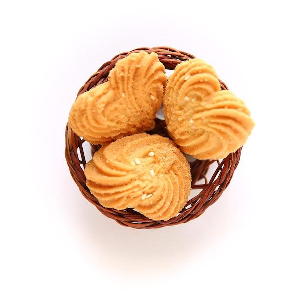 Biscotti a forma di cuore con cesto di legno su sfondo bianco